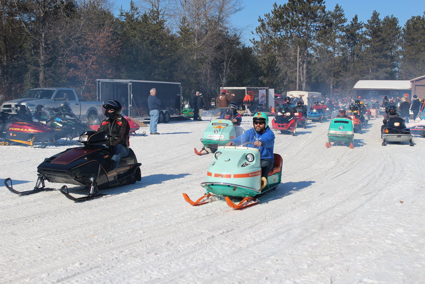 Riders line up their vintage sleds at the beginning of a trail ride.