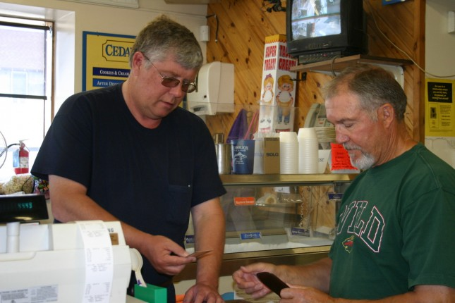 Vermilion Fuel & Food owner Dave Sorensen (left) helps a customer.