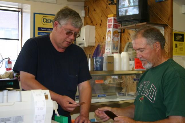 Vermilion Fuel & Food owner Dave Sorensen (left) helps a customer.