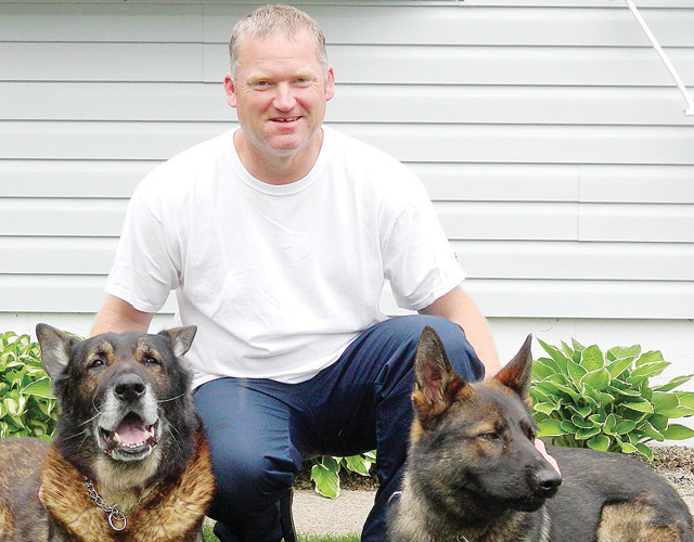 Deputy Tim Officer posed with two of his law enforcement dogs for a 2014 story in the Timberjay.