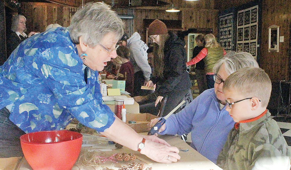 Folk School instructor Pat Miller shows students Gloria Bowen and her eight-year-old grandson Ace Bowen how to construct a pine cone Christmas ornament during a recent class at the Ely Folk School.