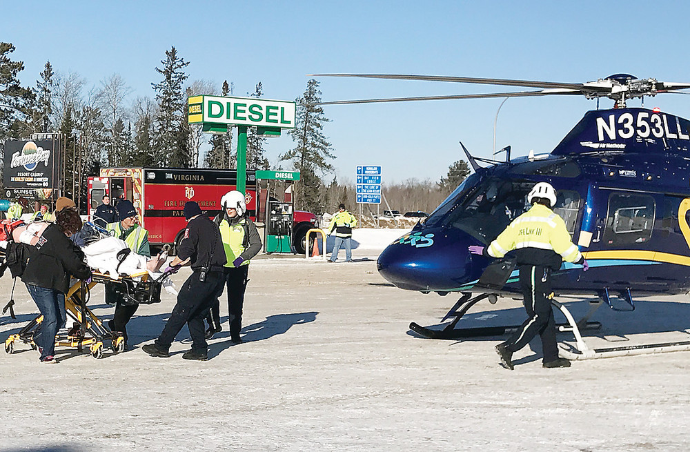 Medical personnel from Tower and Virginia ambulance services and the Lifeflight air ambulance roll their patient towards the helicopter in the Y Store parking lot. The crash took place around 11 a.m. on Sunday morning.