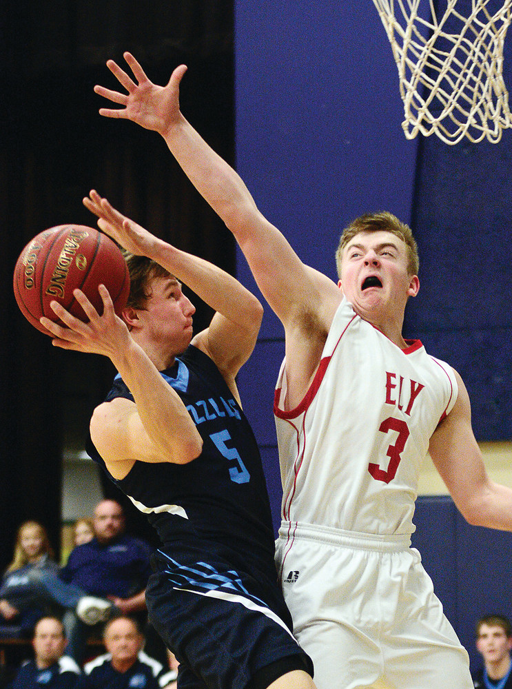 Ely's Carter Gaulke reaches high to block a shot from the Grizzlies' Brendan Parson during Tuesday night's tilt at North Woods.