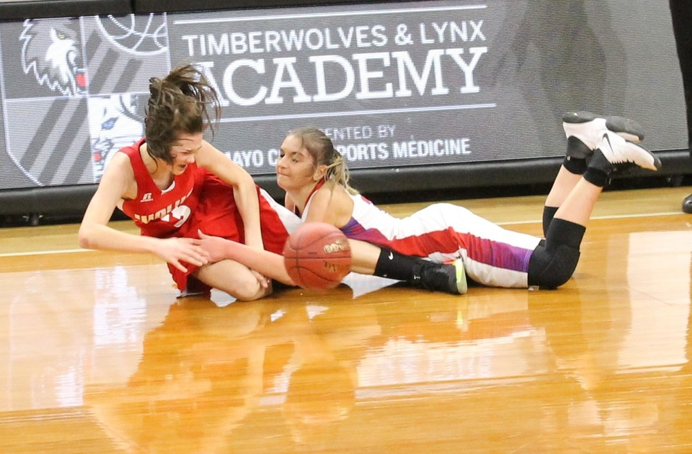 Ely freshman Brielle Kallberg, left, battles for possesion of a loose ball during Saturday's game against Chisholm at Target Center in Minneapolis.