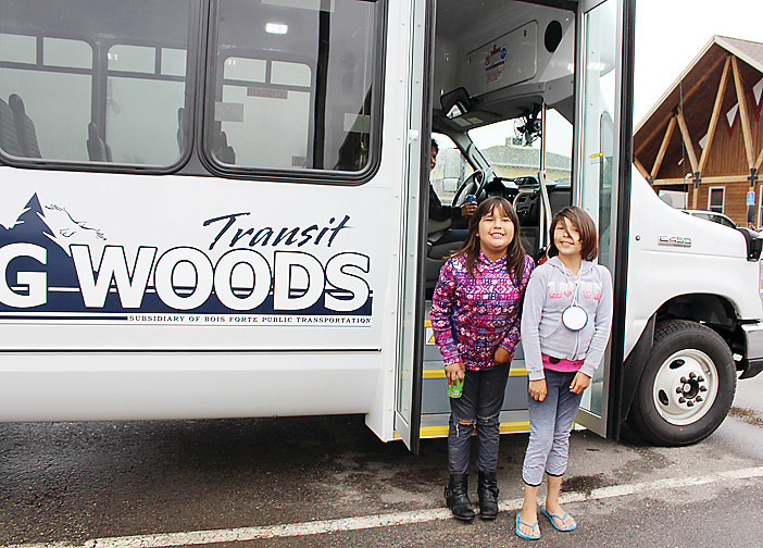 Two young Vermilion residents, Sophia Medicine and Rena Boshey, pose for the camera outside one of the new buses that were on display at both the Nett Lake and   Vermilion sectors this past week.