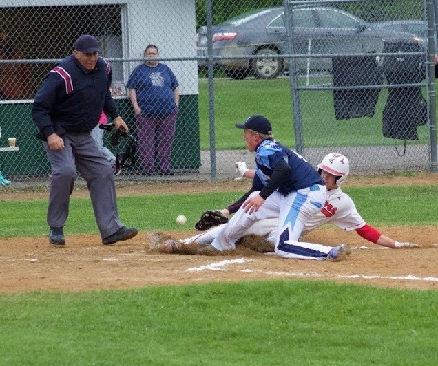 Ely senior Mark Killoran slides safely into the plate to score on a first-inning wild pitch ahead of the tag by North Woods junior Tate Olson. Killoran finished the night 3-for-4 with two runs and an RBI to help lead the Wolves to a 10-0 win.