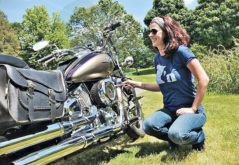 Leah Phifer inspects her Vstar motorcycle, which she plans to ride throughout the Eighth District over the next 80 days as part of a listening tour.