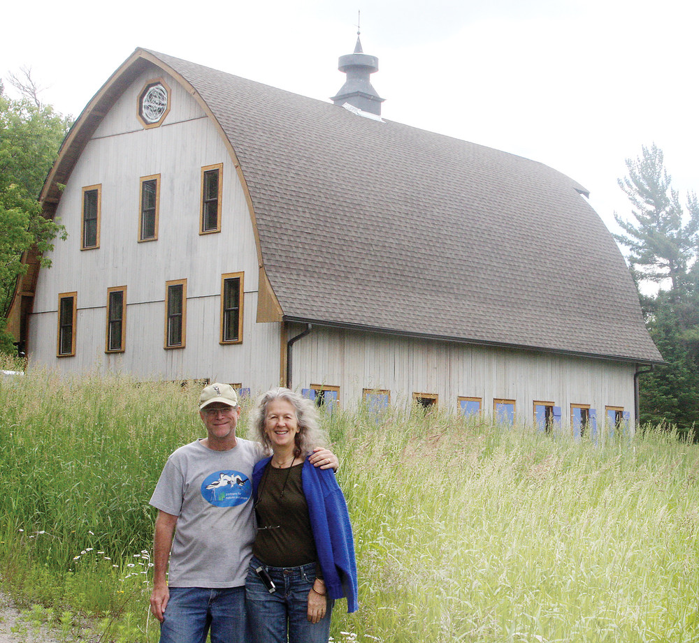 David Stanton and Sharon Beatty with their barn turned dream home in the background.