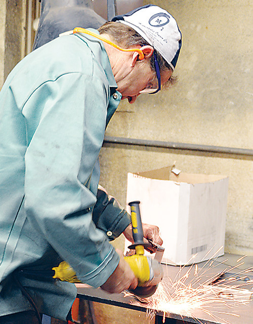 Daryl Lamppa, owner of Lamppa Manufacturing, grinds a wood furnace part at the Tower shop. The company's product exceed federal pollution standards by nearly 40 percent.