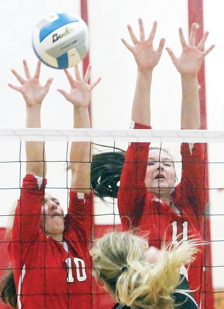 Freshman McKenna Coughlin and sophomore  Brielle   Kallberg put all their fingers to work in an effort to block a hit by Northeast Range senior Melissa Nelmark.