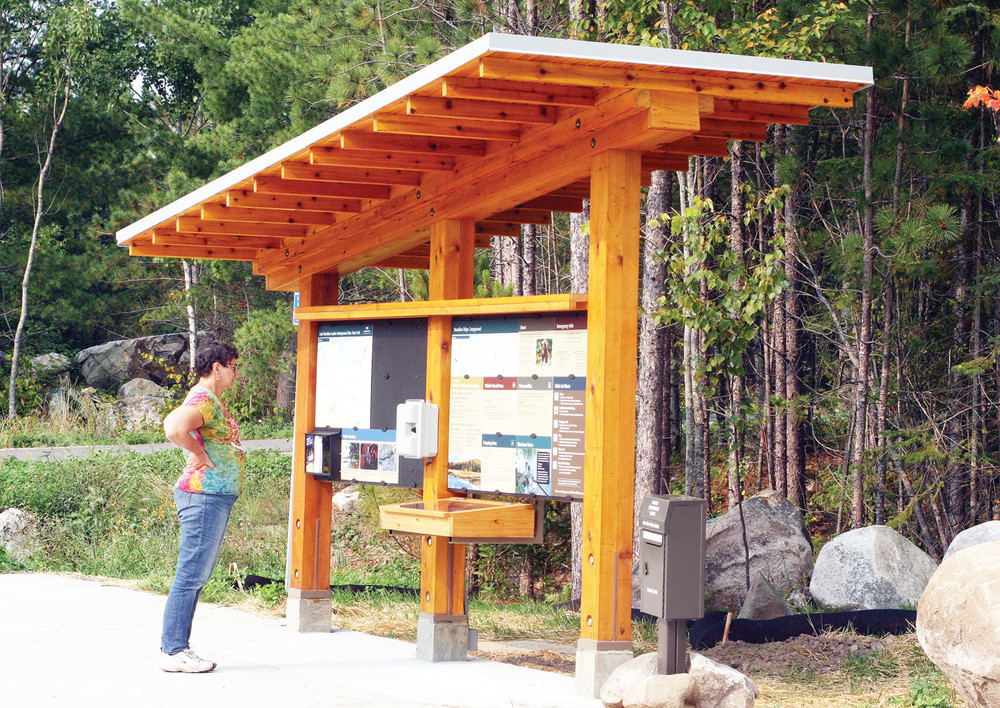 A camper looks over information at the Lake Vermilion Soudan Underground Mine State Park campground pay station.