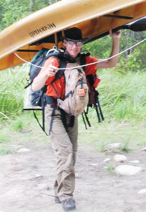"""Robert """"BeaV"""" Vollhaber gives a thumbs while portaging along the route."""