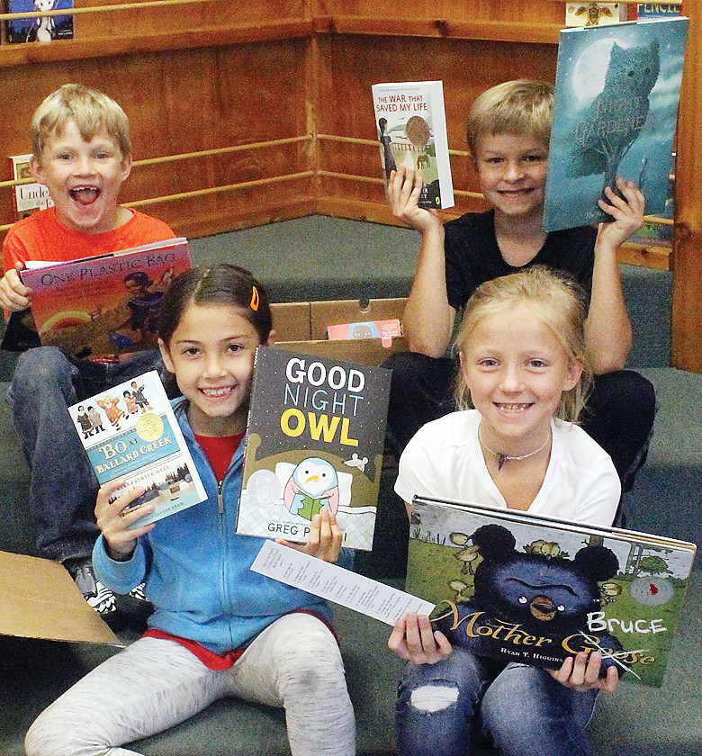 Four Ely Washington second-graders, Logan Kainz, Dawson Murphy, Stella Koivisto and Saylor Sandberg, opened boxes   of books last week for the Minnesota Young Readers program.