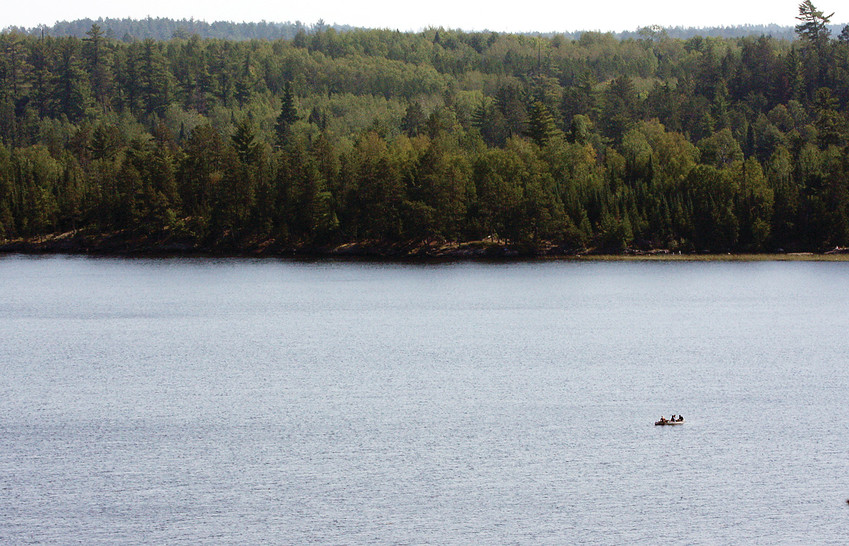 A lone canoe makes its way across Nina Moose Lake in the Boundary Waters Canoe Area.