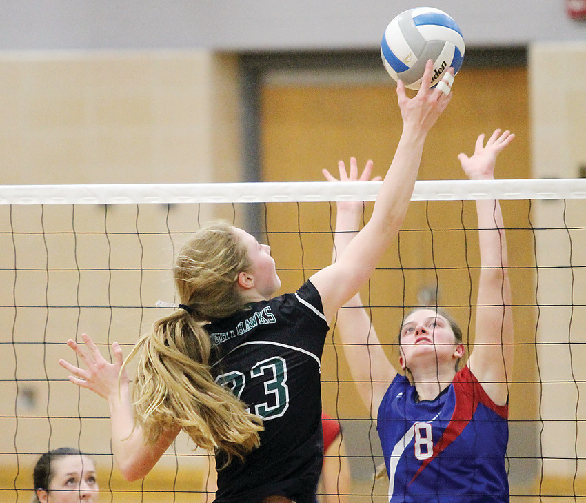Nighthawks' Hannah Reichensperger taps the ball over the net, above the outstretched hands of Chisholm's Rylee   Appelman.