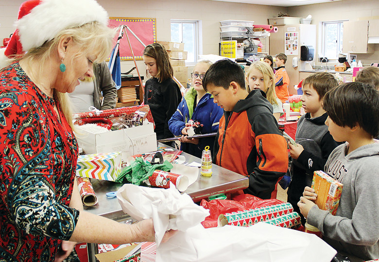 "Cindy Myre, who helped start ""Santa's Workshop,"" volunteers to help children wrap presents."