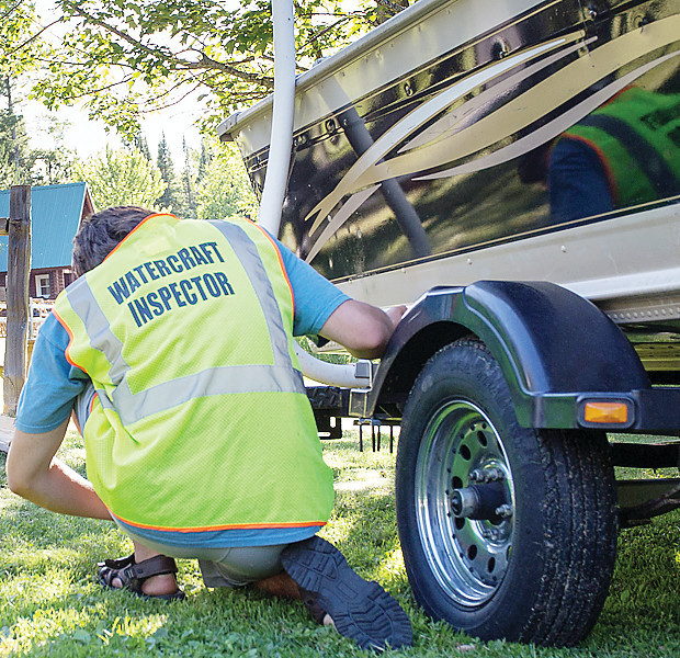 A boat inspector checks for aquatic invasive species on a boat and trailer at Pehrson Lodge on Lake Vermilion.