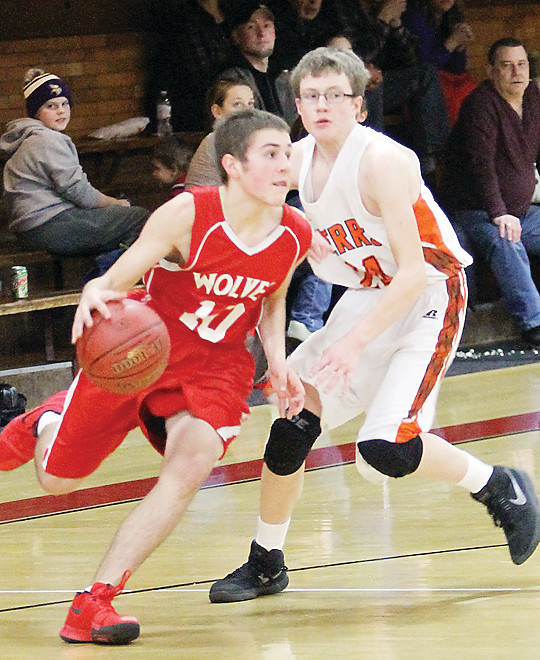 Ely sophomore guard Eric Omerza races by a Cherry defender.