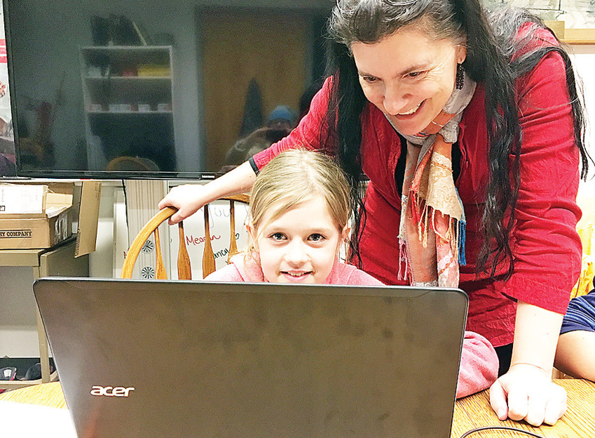 Theresa Drift instructs Rory on a coding program with computers that were purchased with funds from the Blandin Foundation for the purpose of increasing reliable broadband internet access and teaching computer education throughout the Grizzlies Broadband Community.
