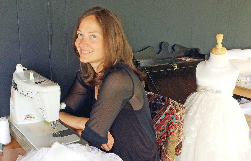 Beth Ohlhauser, owner, designer and seamstress of Olive and Fern, creates custom-designed girls' dresses in her sewing shop in Ely.