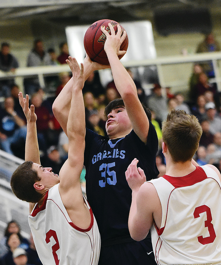 The Grizzlies' Trevor Morrison takes a jump shot under pressure from Ely's Patrick Vanderbeek and Carter Gaulke.