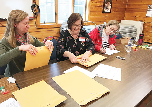 Carol Maus, election judge, Sue Drobac, town clerk, and Mary Richard, election judge, seal the ballots after the Greenwood Township election recount last Friday.