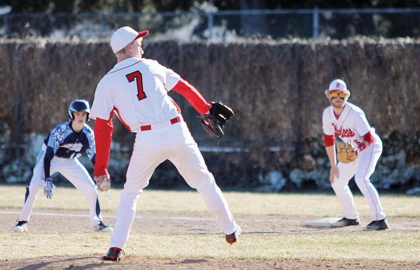 Ely pitcher Trevor Mattson winds up while other   players look on.