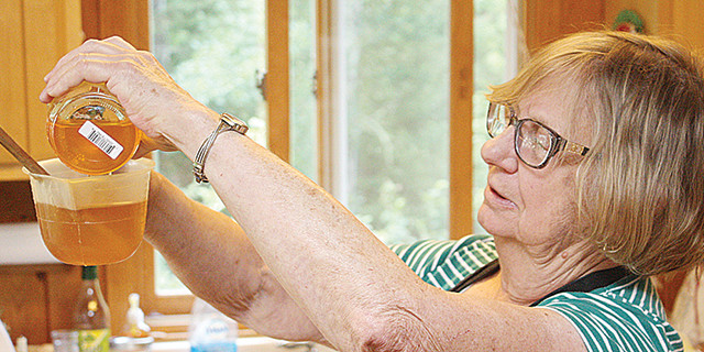Ely Folk School instructor Mary Louise Icenhour measures out a portion of her honey for a batch of walnut poticas.