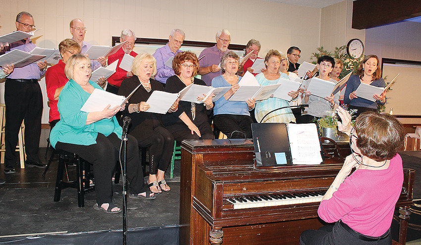 Jan Kimes directs the choir as it sang songs with a Minnesota theme.