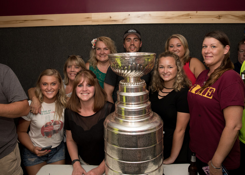 "Washington Capitals hockey player Matt Niskanen, a 2005 graduate of Mt. Iron-Buhl High School, brought the Stanley Cup to his family's Lake Vermilion cabin and The Vermilion Club on July 22. He is shown with VC owner, left, Greg ""Arch"" Archibald and the VC staff, above."