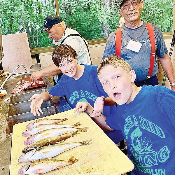 Young anglers seem rightfully impressed with their catch.