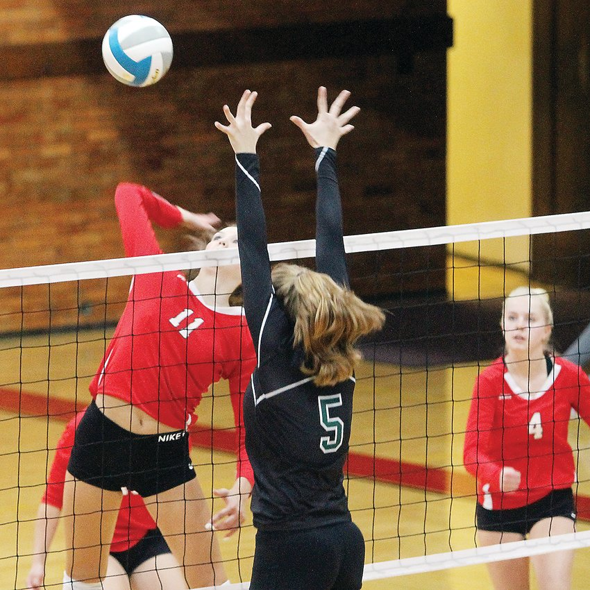 Nighthawks sophomore Hannah Reichensperger, #5,  goes up high to block a shot from Ely senior Brielle Kallberg during action Tuesday night in Ely.