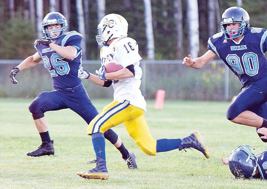 Nathan Crain and Trevor Morrison chase after Rush City's Zeth Hahn during last Friday's contest at the North Woods School. Hahn rushed for 224 yards to lead the Tigers to a 34-8 win.