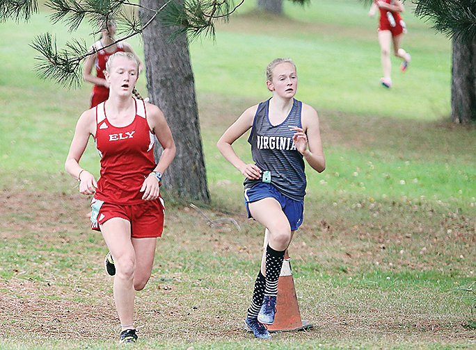 Ely's top girls finisher, Zoe Devine, kept pace with a Virginia runner during Tuesday's meet at the Ely Golf Course.