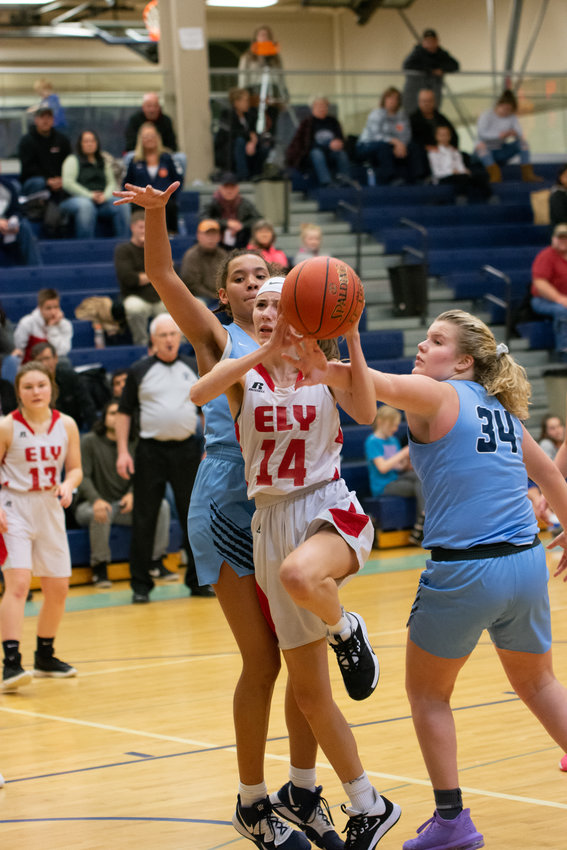 Ely freshman Madeline Perry takes aim at the basket as she gets tangled up with the Grizzlies' Brynn Simpson and Hannah Kinsey.