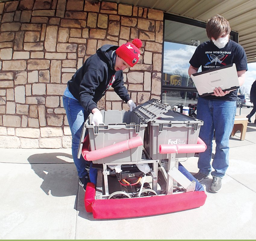"""Ely robotics students Raif Olson and Caleb Kappes-Bliss, above, sanitize and program a """"grocery 'bot"""" at Zup's Market."""