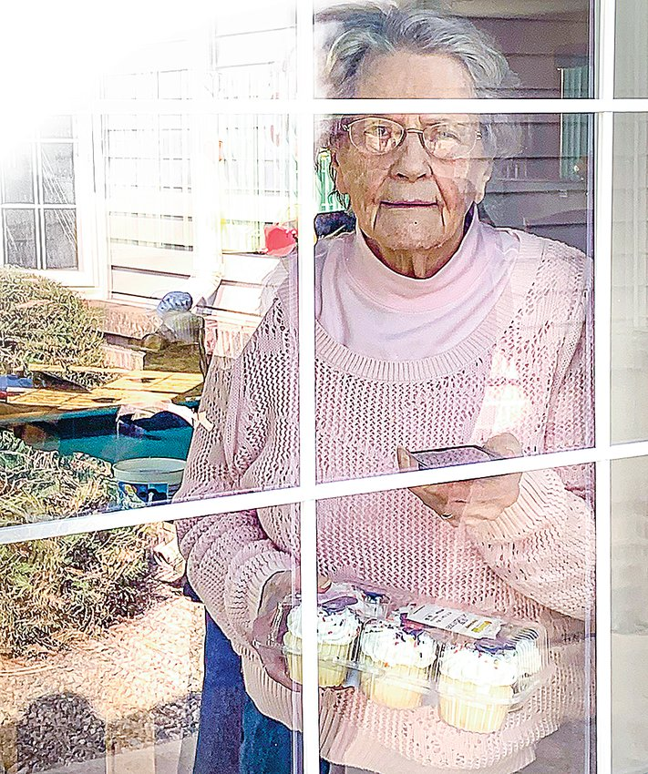 "With cupcakes and cell phone in hand, Elsie Dahl looks out the window at Edgewood Vista in Virginia as family and friends outside sang ""Happy Birthday"" to mark her 91st birthday on April 23."