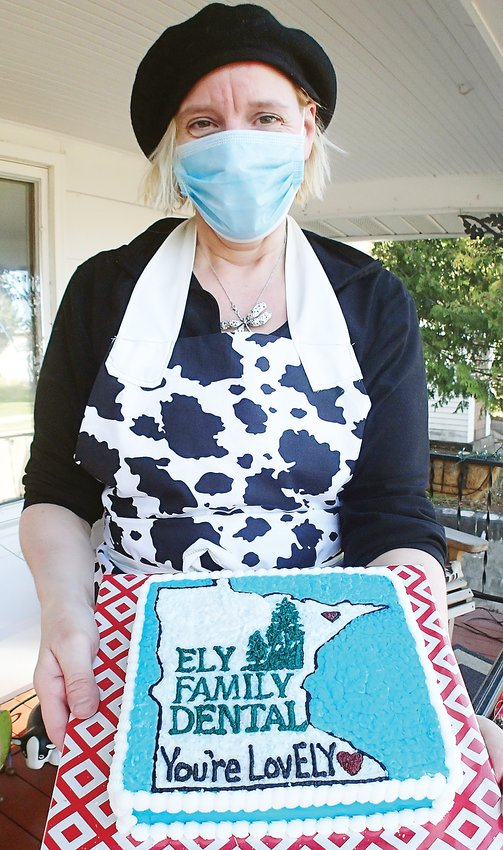 A masked Susan Laine displays another cake she baked this week, destined for an Ely business.