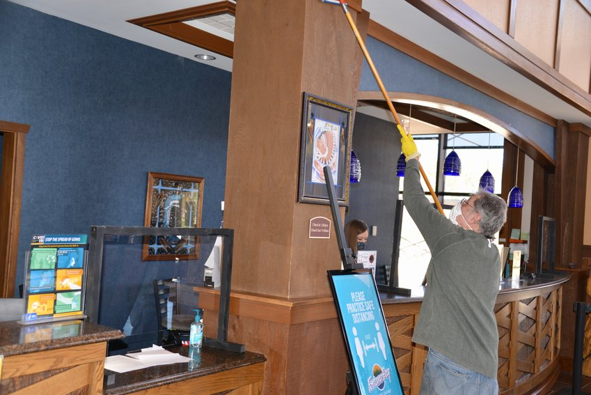 Fortune Bay's Nick Miller, a Hoyt Lakes resident, is shown cleaning walls near the resort front desk. Also pictured is Rebecca Stahl, a Virginia resident, who is Fortune Bay's front desk manager.