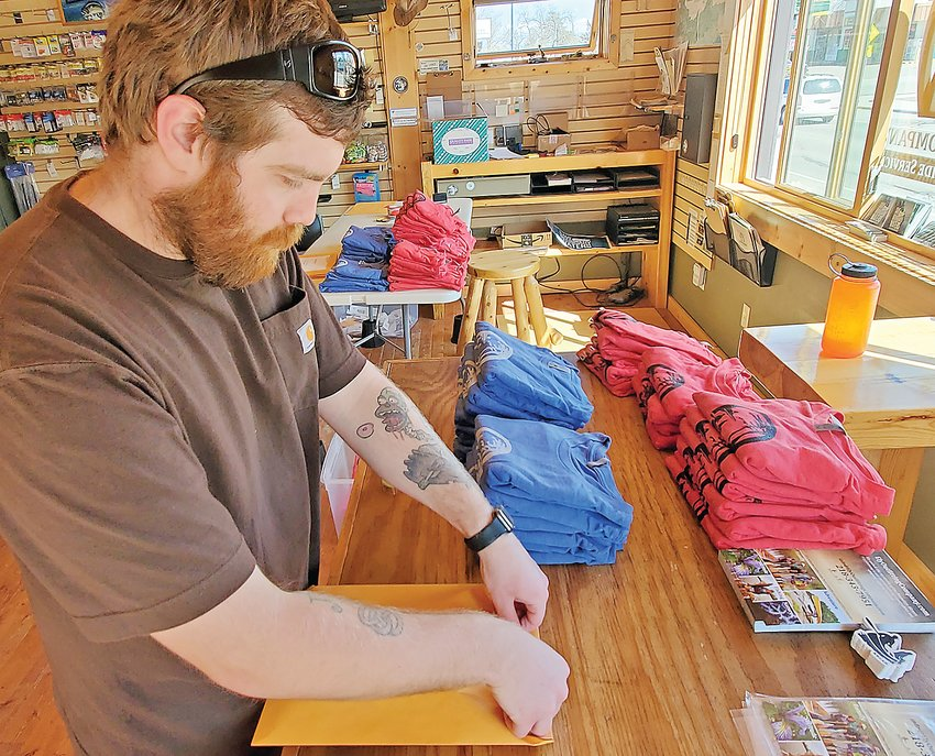 Nick Bailles, of Ely Outfitting, packages t-shirts made famous by a new best-selling romantic comedy.