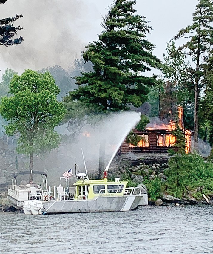 Greenwood Township Fire Boat 1 works to control the spread of a fully-engulfed cabin fire Saturday morning on Nelson Road.