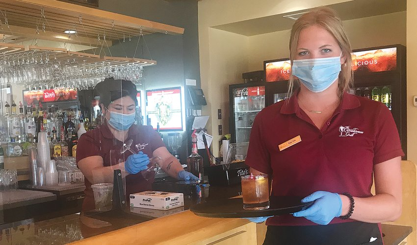 Bartender Joett Baldwin, left, and server Kaylee Iverson wear protective face masks and gloves while serving guests at the Wilderness Grill at Fortune Bay Resort Casino.