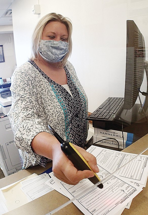 Ely Deputy Clerk Casey Velcheff scans ballot bar codes Monday as she registers a stack   of absentee ballots.