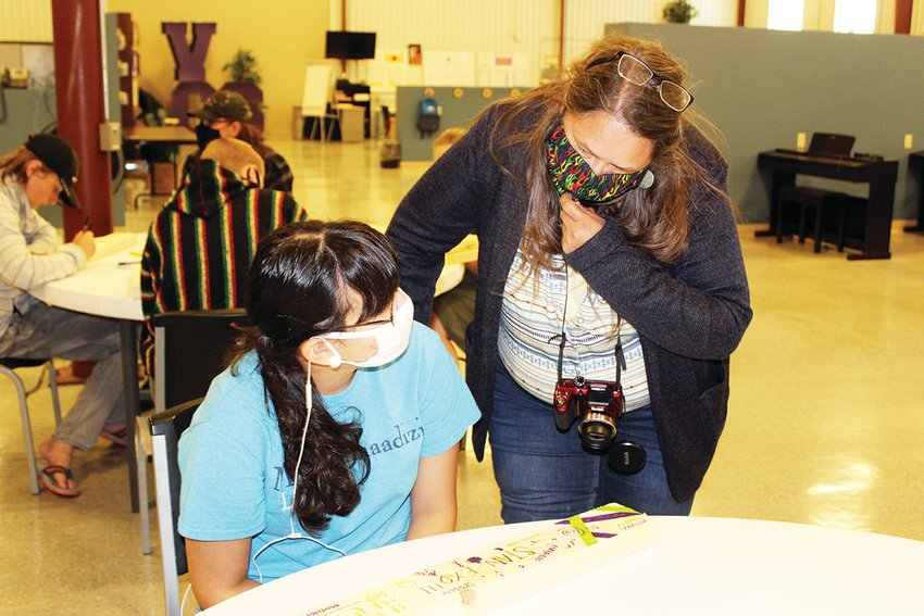 Paraprofessional Michelle Maki talks with Alliyah Zapata, who is decorating the wood that will be used to build her bench.