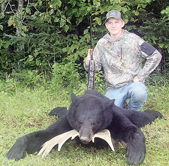 Sixteen-year-old Troy Ray  poses with the 326-pound bear he shot during the first week of the 2020 bear hunt.