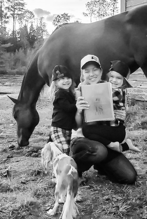 "Sporting a signature Badass Rodeo Company hat and holding a copy of her book ""Barrel Racing IS Life,"" Laura Julkowski poses with her  daughters Chesney, 5, and Harley Jo, 3."
