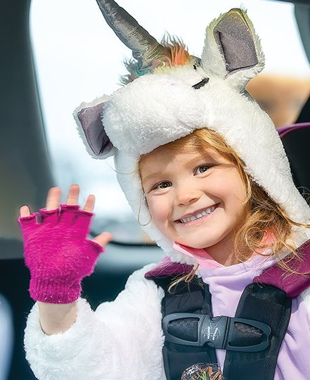 Cora Lantry, dressed up as a unicorn, waves from a car at the Cook Lions Club drive thru candy handout in Cook.