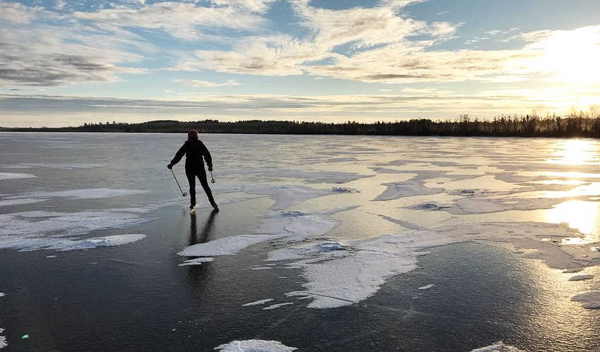 A skater glides across the surface of Lost Lake, near Tower, on a recent late afternoon.  The lake had about nine inches of clear ice as of this week.