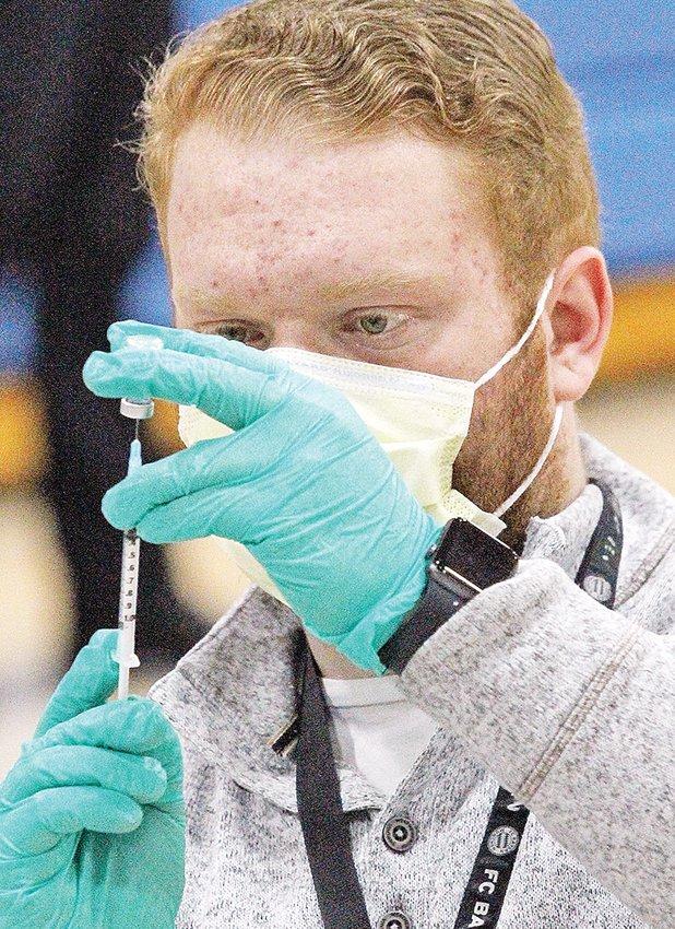 Pharmacist Chris Schneider fills a syringe.
