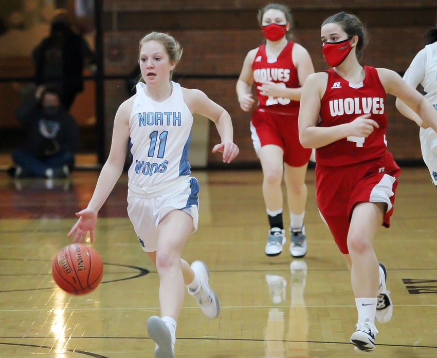 North Woods' Helen Koch dribbles down the court with Ely's Holly Dirks in hot pursuit.